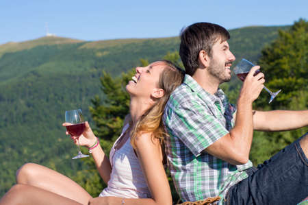 wine background: Young happy couple drinking wine on a hiking trip at the viewpoint. Couple hiking trip