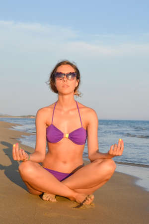 Girl in bikini meditating on the beach facing the sunset