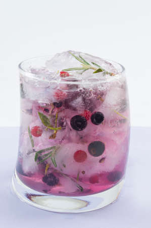 cold background: Natural homemade red forest fruit iced-T juice with ice, lemon and sliced fruits