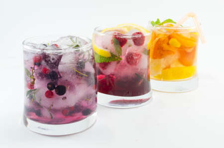 non alcoholic: Three non alcoholic fruit cocktails with iced and sliced fruit on white background. Cold summer beverage Stock Photo