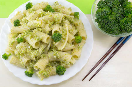 Cooked pasta with broccoli served with cooked broccoli in a white bow on a wooden table. Eating with chopsticks Banco de Imagens
