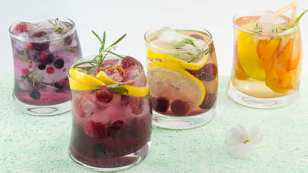 crooked: Natural fruit iced-T juice with ice, lemon and sliced fruits in a crooked glass on blue table with white background