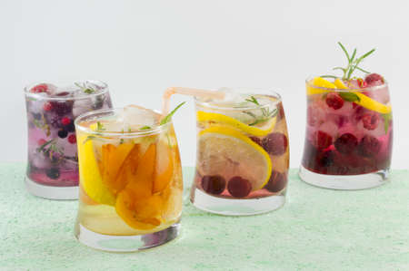 non alcoholic: Four non alcoholic fruit cocktails arranged on the green table with white background. Summer cold beverages.