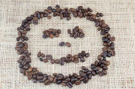 granos de cafe: Cara sonriente hecha enteramente fuera de los granos de caf� colocada en la bolsa de caf� de textura Foto de archivo