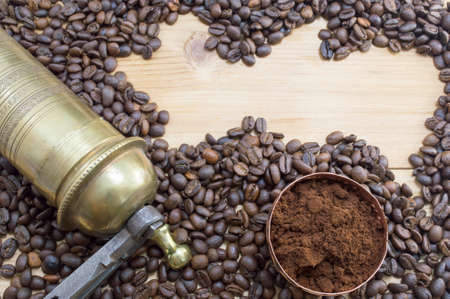grounded: Coffee beans, grinder and on a wooden table with grounded coffe in a coffe cup. Different forms of coffee