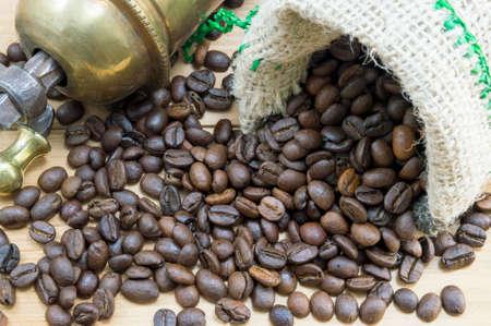frijol: Granos de caf� que caen de la bolsa de caf� junto a un molino de caf� de la vendimia. fondo del caf�