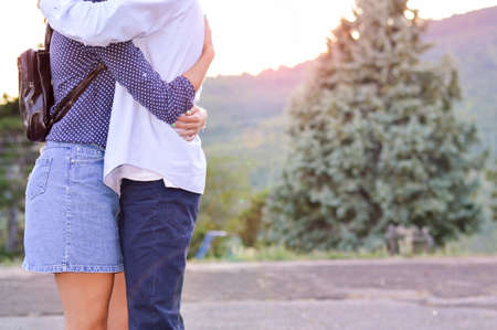romantic hug: Loving couple hugging strong outdoors with no faces shown. Romantic sunset. Lens flare effect Stock Photo