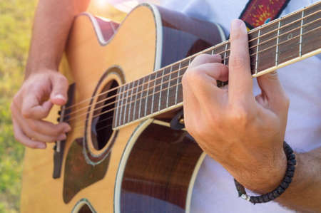 acoustic guitar: Mans hands and fingers playing acoustic guitar in the field