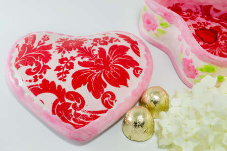 decoupage: Decoupage decorated old  vintage jewelry box with flower pattern next  to flowers and a candy Stock Photo
