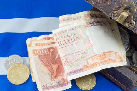 greek currency: Greek old currency drachma banknotes falling out of the box on the Greek flag