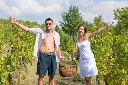 wine grower: Happy brother and sister working on grape picking and holding the wicker basket