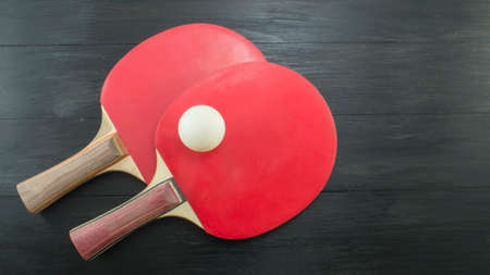 tabletennis: Pair of red table tennis rackets on dark background with copyspace