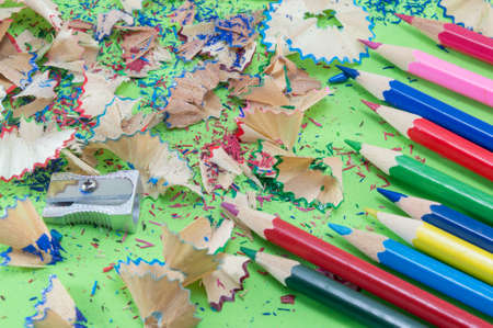 leftovers: Colorful pencils and sharpening leftovers on the green background Stock Photo