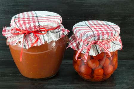 tiendas de comida: Jars of homemade ketchup and cherry tomato on dark background