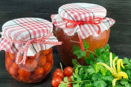 tiendas de comida: Tarros de salsa de tomate casera y tomate cherry próximos al tomate cereza fresca sobre fondo oscuro Foto de archivo