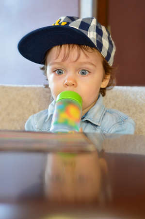 one year old: Cute one year old in cafe  drinking from his bottle