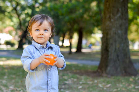 autumn in the park: Adorable one year old child in the park playing with his toy