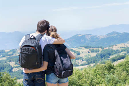 Couple of hikers with backpacks standing at viewpoint and enjoying a valley view. Couples shared activity