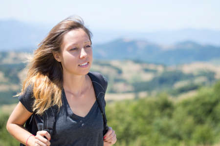 Portrait of happy girl hiker with backpack in the mountains surrounded by green vegetation. Hiking trip