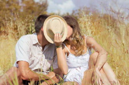 first love: Couple kissing in the field behind a straw hat