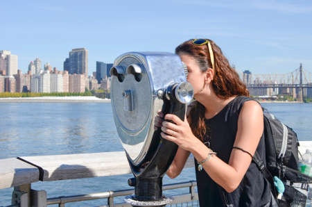 overlook: Girl looking thru public binoculars at the Manhattan view.  Lens flare from bincoulars on a sunny day