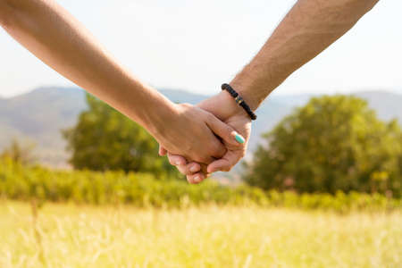 hold hands: Couple holding hands with romantic view at the sunlit field Stock Photo
