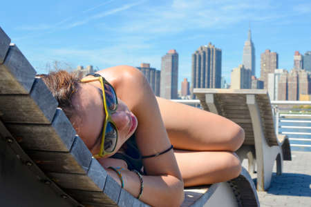 sexy young girl: Girl enjoying Manhattan view lying on the wooden sunbed Stock Photo