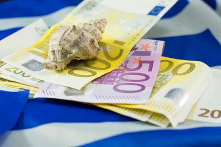 tourism industry: Euro bills on the Greek flag and the shell on top, with low depth of field. Tourism income abstract
