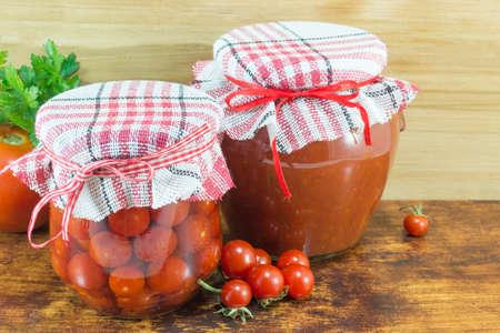 tiendas de comida: Tarros de salsa de tomate casera y tomate cherry próximos al tomate cereza fresca sobre fondo de madera