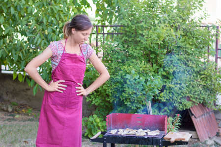 backyard woman: Handsome young woman preparing barbecue in the backyard Stock Photo
