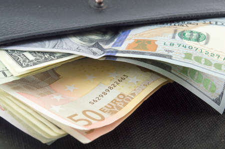 fifty euro banknote: Various euro and dollar bills in a black wallet