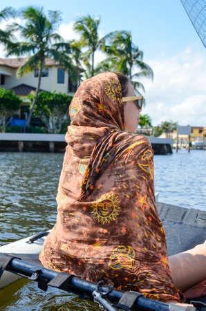 fille arabe: Belle fille couverte avec un foulard hippie navigue la mer, entour� de palmiers