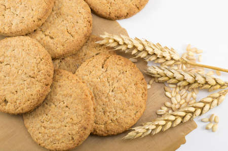 integral: Integral cookies and yellow wheat plant on a brown cooking paper Stock Photo