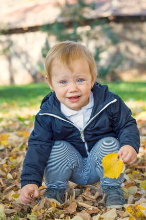 one year: Cute one year old baby girl sitting on grass in a park Stock Photo