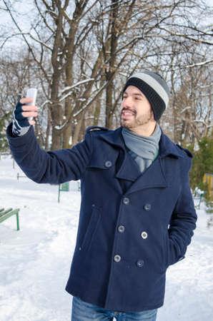 hombre barba: Hombre barbudo joven que toma una selfie en un parque en un d�a soleado de invierno Foto de archivo