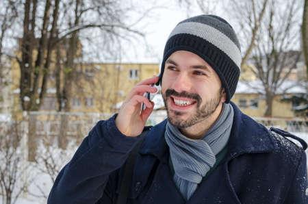 hombre con barba: Hombre barbudo hablando por un tel�fono celular en el invierno