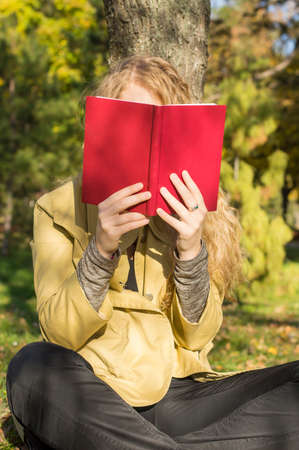 sitting pretty: Blonde girl reading a red book in a park on a sunny autumn day