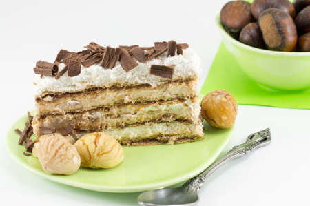 pine kernels: Chestnut cake slice on a green plate served with whole cooked chestnuts