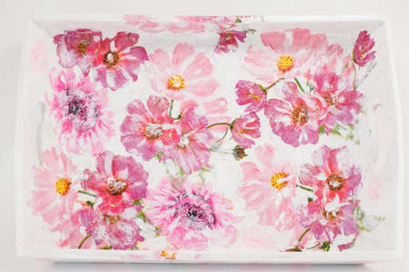 decoupage: Decoupage decorated tray with flower pattern against soft pink background Stock Photo