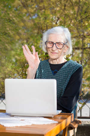 video call: Senior woman having a video call on a notebook computer in the backyard Stock Photo