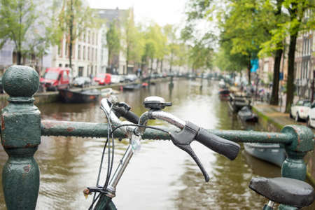 Bicycle parked on a bridge in Amsterdam on a rainy day Banco de Imagens