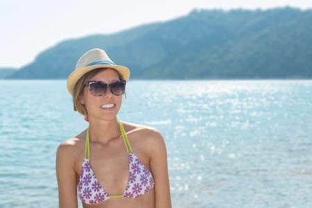 donne mature sexy: Ritratto di una ragazza felice in spiaggia con il sole che splende dietro di lei Archivio Fotografico