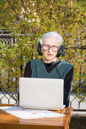 backyard woman: Senior woman having a video call on a notebook in the backyard using headphones Stock Photo