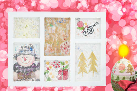Homemade decoupage Christmas decorations in a photo frame with holidays background and a burning candle