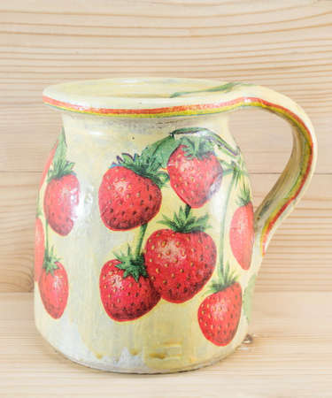 decoupage: Decoupage decorated strawberry pattern pitcher against wooden background