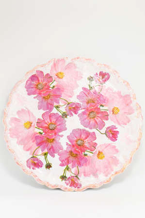 decoupage: Decoupage decorated plate with flower pattern against white wooden background Stock Photo