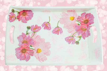 pink background: Decoupage decorated tray with flower pattern against soft pink background Stock Photo