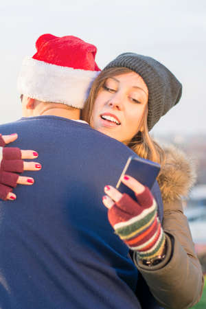 beautiful boy: Girl looks at her smart phone while hugging her boyfriend who wears Santa hat