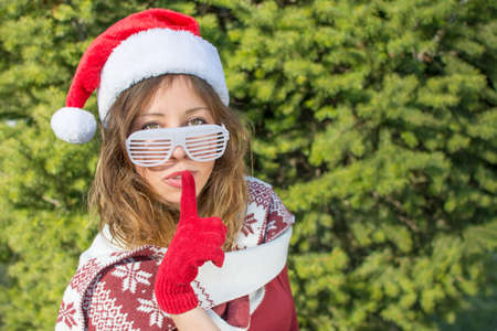 shhh: Beautiful Santa Claus girl with finger on her lips. Shhh!