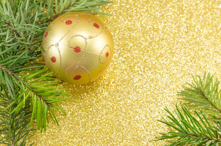 Festive golden colored Christmas ornaments and fir tree background Stock Photo